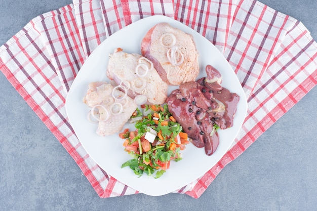 Части сырого мяса и курицы на белой тарелке.