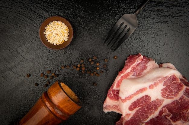 黒い石のプレートに生肉とフォークナイフと塩とコショウ