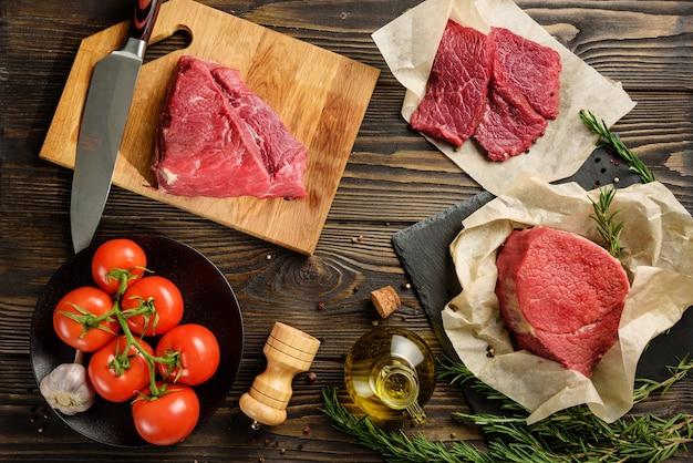 木製のテーブルで調理するための生肉と食材。牛肉を使ったフラットレイコンポジション。