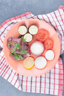 Сырое мясо и нарезанные свежие овощи на оранжевой тарелке.