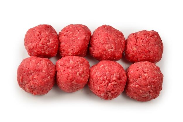 Сырые мясные шарики, изолированные на белом фоне.