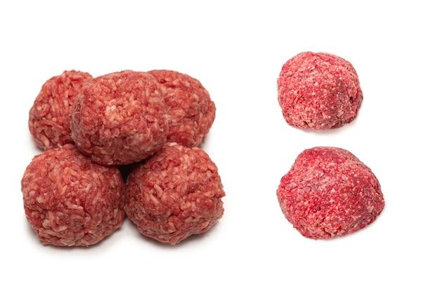 Сырые мясные шарики, изолированные на белой поверхности.