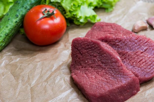 新鮮な野菜の木製の表面と生肉バーベキュー。食べ物、ステーキ、ビーフバーベキュー、トマト、ピーマン、調理用スパイス。