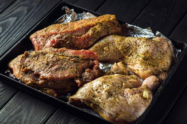 베이킹 시트의 생고기 쇠고기와 닭 다리는 오븐에서 굽기 위해 준비됩니다. 국가 고기 요리는 휴일 전날에 준비됩니다.