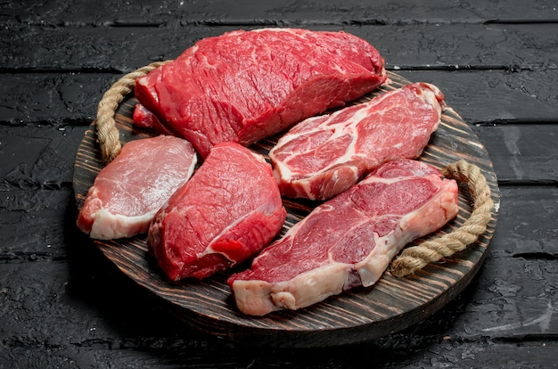 Сырое мясо. стейки из говядины и свинины на деревянном подносе. на черной деревенской поверхности.