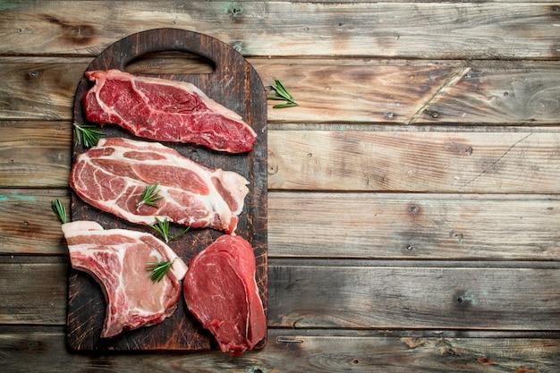 Сырое мясо. стейки из говядины и свинины на доске. на деревянной поверхности.