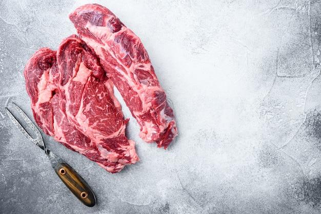 생고기 쇠고기 스테이크. 블랙 앵거스 프라임 고기 세트, 그레이 스톤 테이블, 립 아이 컷, 평면도 플랫 레이