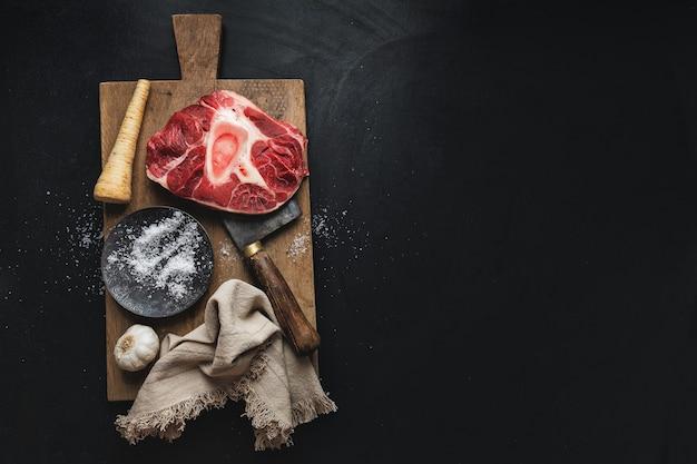 Стейк из сырого мяса из говядины со специями из костей и овощей на темной поверхности