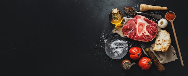 Raw meat beef steak with bone and vegetables spices on dark surface