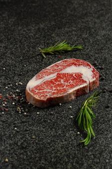 원시 고기, 검은 배경에 향신료와 쇠고기 스테이크