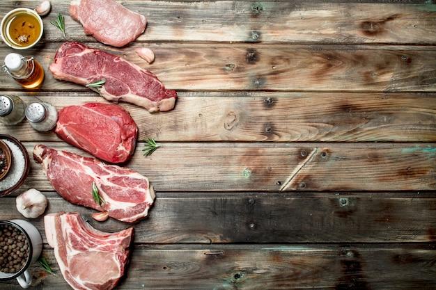 Сырое мясо. стейки из говядины и свинины со специями. на деревянном фоне.