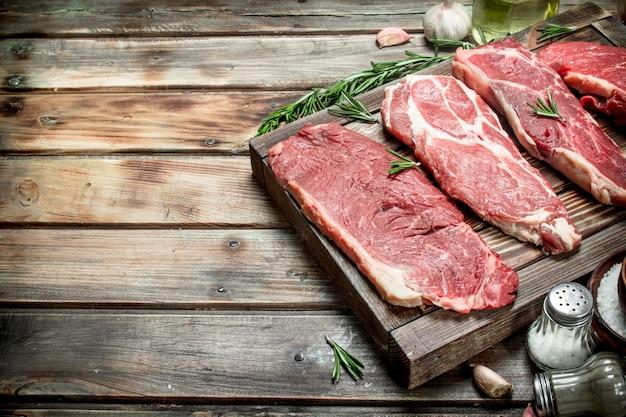 Сырое мясо. стейки из говядины и свинины со специями на деревянном столе.
