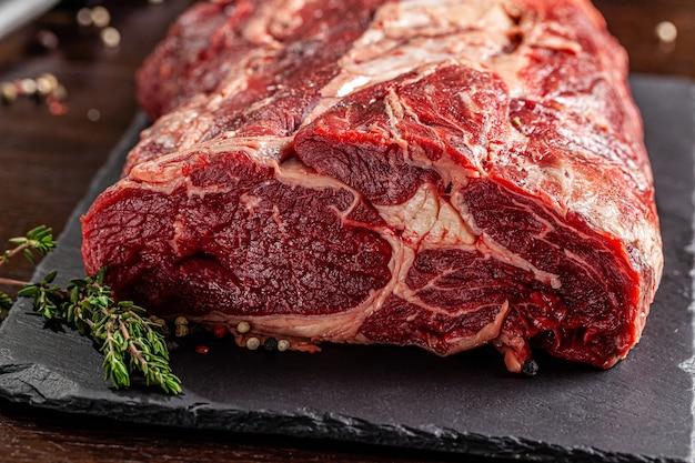 생고기. 쇠고기 안심, 목은 칼과 칼 깎이 옆에있는 블랙 보드에 있습니다. 확대. 배경 이미지. 복사 공간