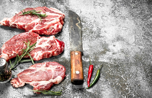 Raw meat of beef with rosemary and hot peppers. on rustic background.