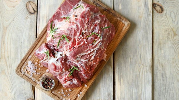 Raw meat on a board with salt and spices. pork neck.