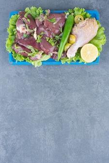 Carne cruda e coscia di pollo a bordo blu.