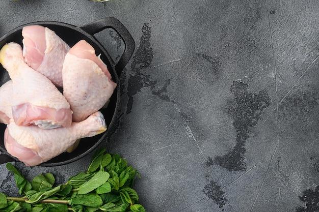 Сырое мясо. куриные ножки, набор нарезок голеней, на сковороде, на сером фоне, плоская планировка, вид сверху, с местом для текста