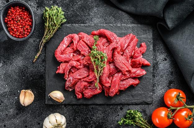 Сырое мясо нарезать тонкими полосками для бефстроганов на черном столе.