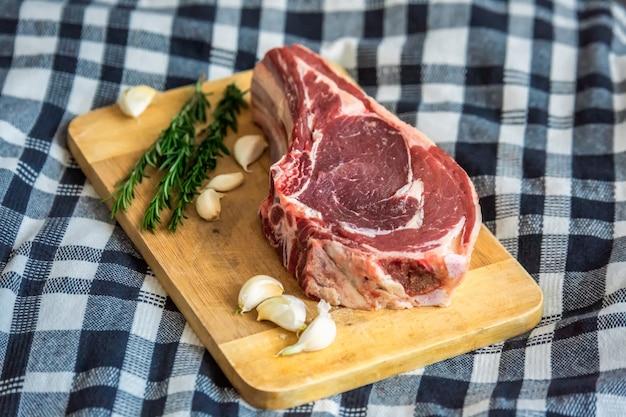 Сырое мясо нарезать с гаймом, чесноком и розмарином на разделочной доске, вид сверху