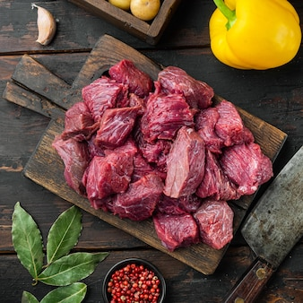 Raw meat diced for stew set with sweet bell pepper, on old dark  wooden table, square format