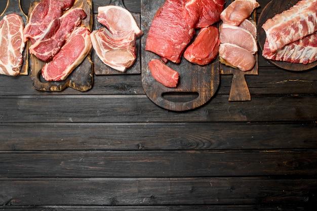 생고기. 나무 테이블에 돼지 고기와 쇠고기 고기의 다른 종류.