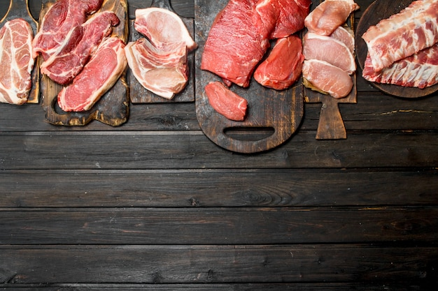 Raw meat. different kinds of pork and beef meat on a wooden table.