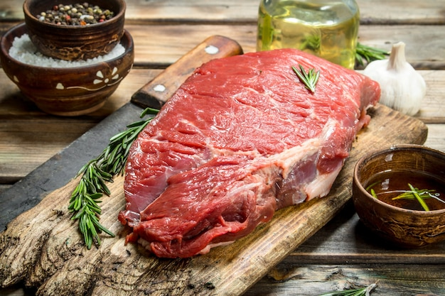 Raw meat. fresh beef on a cutting board with herbs and spices. on a wooden surface.