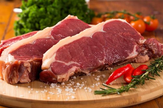 Сырое мясо: свежее филе говядины с чесноком и зеленью на борту.