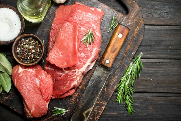 Raw meat. fresh beef with spices and an old knife. on a wooden surface.