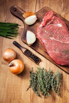 Carne cruda dalla macelleria su tavola di legno con ingredienti. cipolle crude. erbe verdi.
