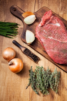 Сырое мясо из мясной лавки на деревянной доске с ингредиентами. сырой лук. зеленые травы.