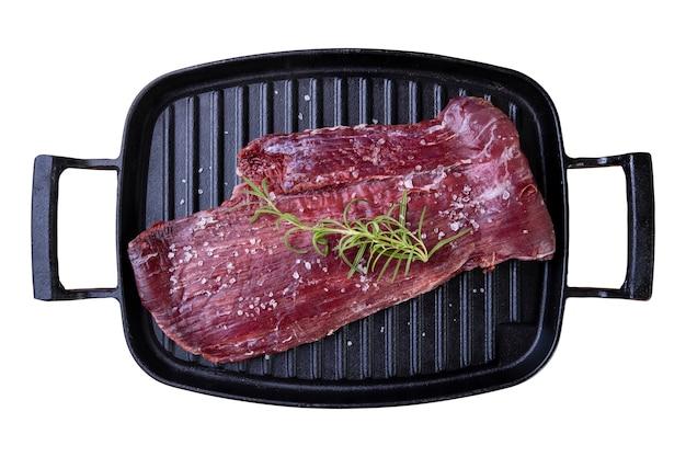 흰색 표면에 로즈마리 분기와 주철 접시에 생고기.