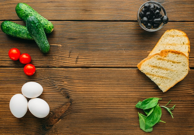 Сырое мясо в приправе, оливки, зелень и яйца