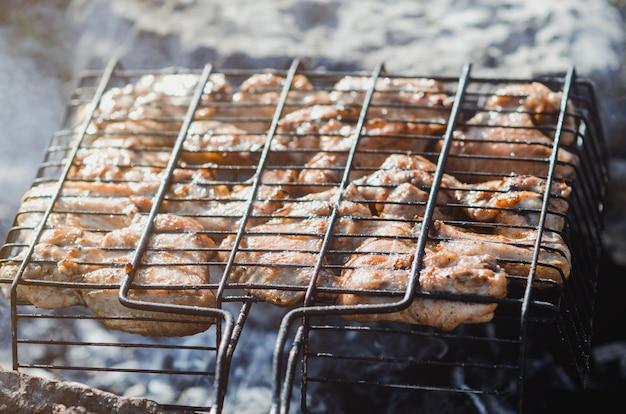 Сырое мясо в решетке лежит на бревне, замаринованное майонезом и приправами.