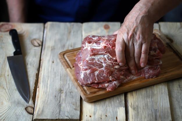 木の板にシェフの手で生肉