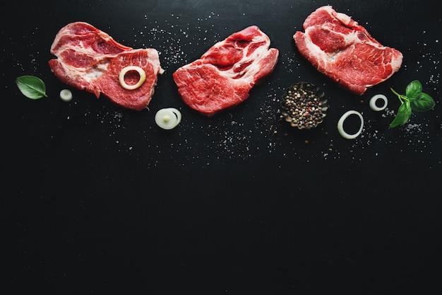 Сырое мясо на борту со специями и зеленью на борту на темной поверхности