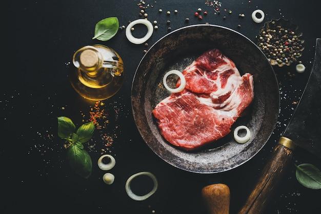 Сырое мясо на сковороде со специями и зеленью на борту на темной поверхности