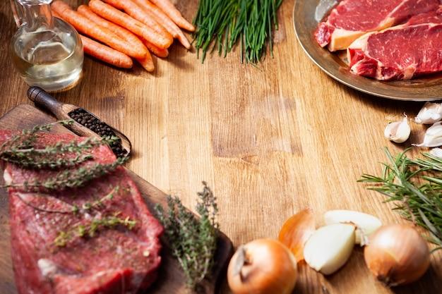 Сырое мясо на деревянной разделочной доске и винтажная тарелка с сырыми овощами, помещенными в круг с пустым пространством посередине. чесночный ароматизатор. зеленые травы.