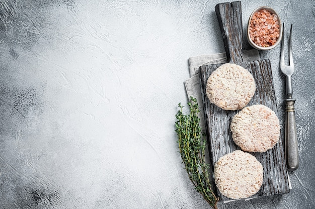 木製のまな板にパン粉を添えた生肉のパテカツレツ。白いテーブル。上面図。