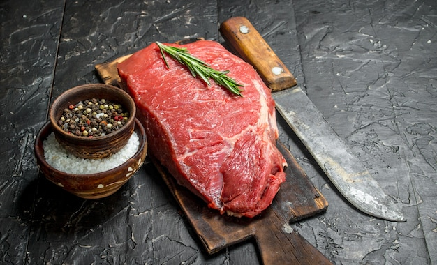 Raw meat. a piece of beef with spices and rosemary. on a black rustic table.