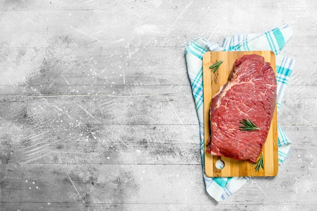 Raw meat. a piece of fresh beef on a cutting board with napkin. on a rustic background.