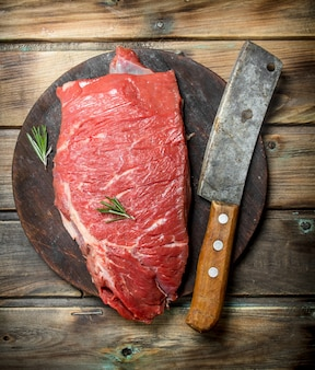 Raw meat. a piece of fresh beef with a hatchet on an old cutting board. raw meat on a wooden table.