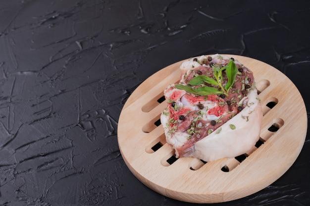 暗い背景に新鮮なミントで飾られた木の板の生肉片。