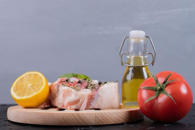 Кусок сырого мяса с лимоном, помидорами и бутылкой масла на черном столе.