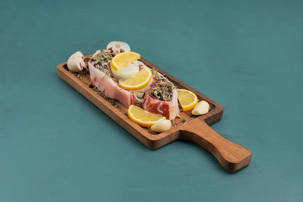 木の板に野菜と生肉片。