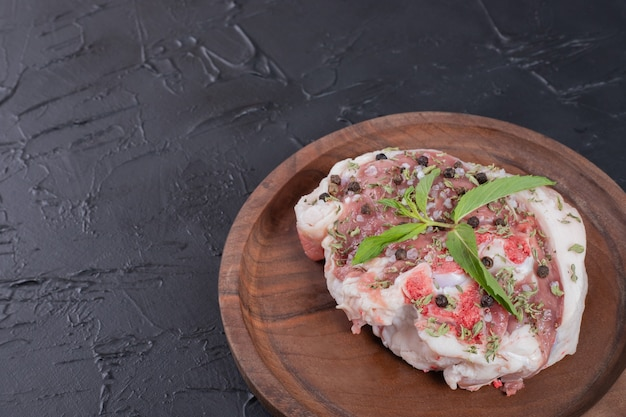 Raw meat piece on wooden plate decorated with fresh mint on dark background.