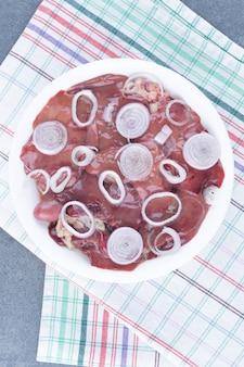 白い皿に生肉と玉ねぎのスライス。
