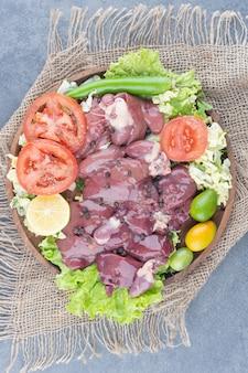 Кусочки сырого мяса и овощей на деревянной тарелке.