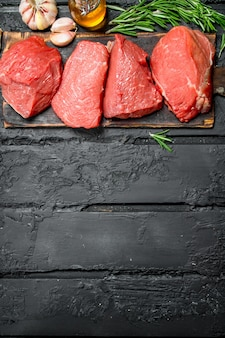 Raw meat. pieces of beef with garlic and rosemary. on a black rustic.