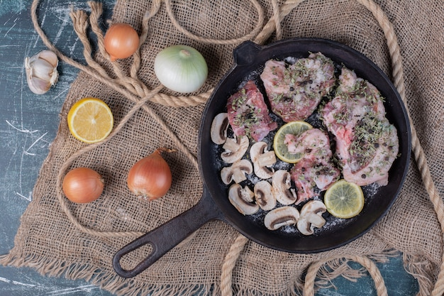 Raw meat pieces in black pan with onions, garlic, lemon and mushrooms.